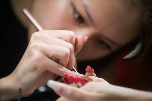 Competitor Cindy Yuen works on the nails of a model at the Canada Nail Cup in Vancouver, Monday, February 16, 2015. (Photo by Darryl Dyck/AP Photo/The Canadian Press)