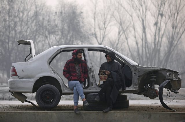 Men chat as they sit in a half-dismantled car along a roadside on a cold winter morning in Srinagar, December 31, 2015. (Photo by Danish Ismail/Reuters)