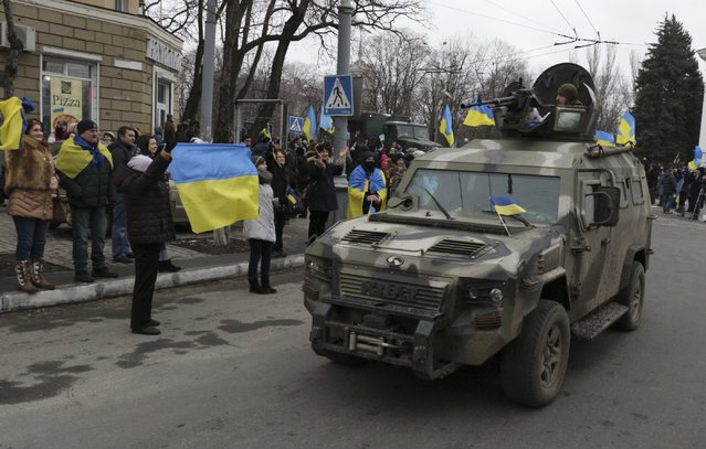 Residents wave Ukrainian flags as they cheer Ukrainian troops coming back to their headquarters after combat operations against Russia-backed separatists in Mariupol, Donetsk region, Ukraine, Wednesday, February 11, 2015. (Photo by Sergey Vaganov/AP Photo)