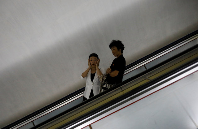 A woman reacts as she rides the escalator at a subway station in Pyongyang, North Korea on September 11, 2018. (Photo by Danish Siddiqui/Reuters)