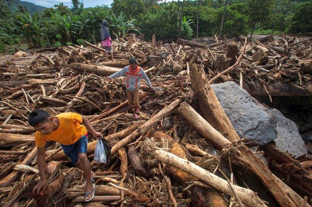 People walk through a pile of tree trunks after flash floods triggered by tropical cyclone Seroja in East Flores, East Nusa Tenggara province, Indonesia on April 7, 2021. (Photo by Aditya Pradana Putra/Antara Foto via Reuters)