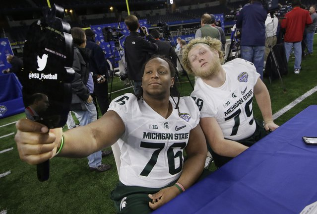 Michigan State offensive linemen Donavon Clark (76) and Kodi Kieler (79) make a photo of themselves during the media day for the NCAA Cotton Bowl college football game Tuesday, December 29, 2015, in Arlington, Texas. (Photo by L.M. Otero/AP Photo)