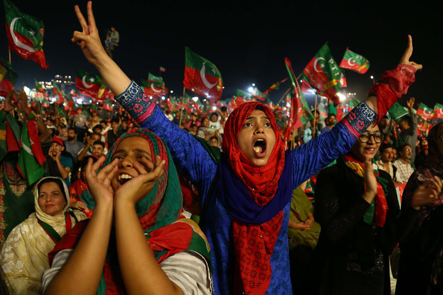 Supporters of Imran Khan, head of Pakistan Tehrik-e-Insaf (PTI) political party listen to his speech, during an election campaign in Karachi, Pakistan, 22 July 2018. Pakistan is set to hold general and provincial elections on 25 July with around 105 million people registered to vote, according to the election commission. (Photo by Shahzaib Akber/AFP Photo)