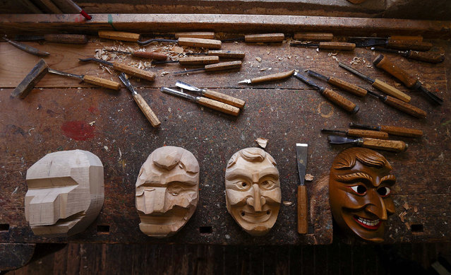 """Traditional carnival mask at various stages of being carved by woodcarver Andreas Lang lies on a work bench at his studio in Elzach in the Black Forest February 14, 2015. The traditional Elzach Carnival parade with its fool caracter called """"Schuttig"""" (""""Ghastful"""") which dates back to the year 1530, is to exorcise the winter. (Photo by Michael Dalder/Reuters)"""
