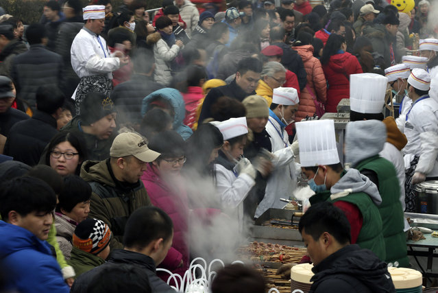 Visitors buy BBQ mutton sticks at the temple fair during Chaoyang Park's International Spring Carnival for the Lunar New Year celebration in Beijing Saturday, February 21, 2015. (Photo by Andy Wong/AP Photo)