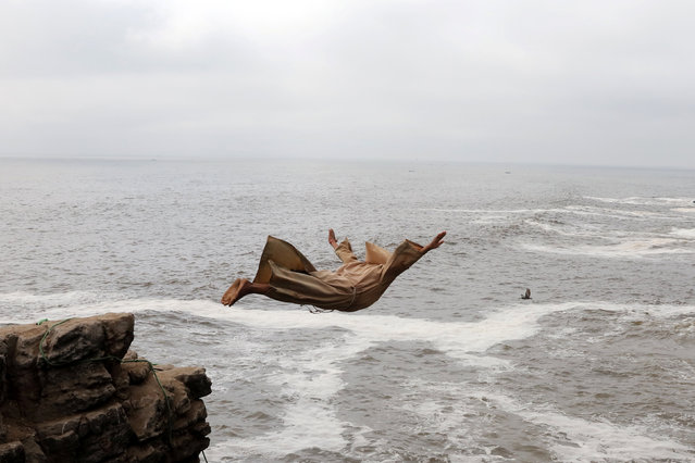 Fernando Jesus Canchari, dressed as a friar, jumps from a 13-meter high cliff along Herradura Beach in Lima, December 7, 2016. (Photo by Guadalupe Pardo/Reuters)