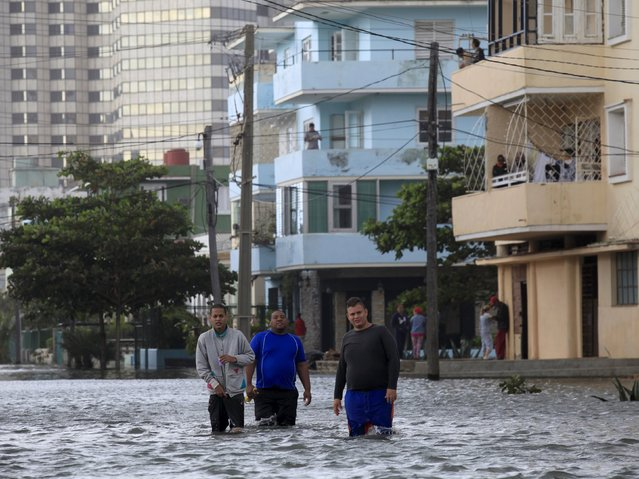 Cubans walk through a flooded street in Havana January 23, 2016. (Photo by Enrique de la Osa/Reuters)