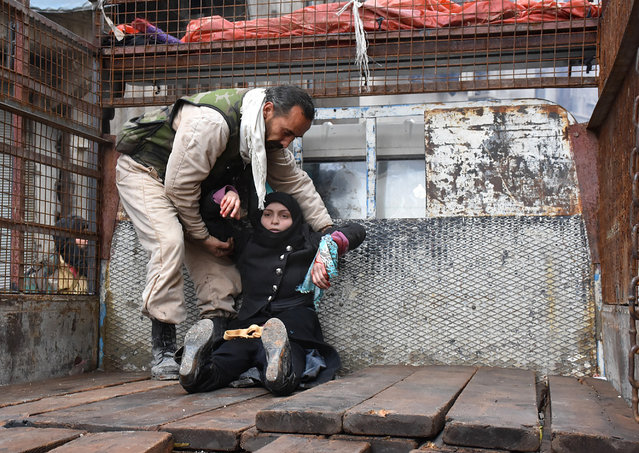 A wounded Syrian woman from the al-Sukari neighbourhood is helped onto the back of a truck as she flees during the ongoing government forces military operation to retake remaining rebel-held areas in the northern embattled city of Aleppo on December 14, 2016. Shelling and air strikes sent terrified residents running through the streets of Aleppo as a deal to evacuate rebel districts of the city was in danger of falling apart. (Photo by George Ourfalian/AFP Photo)