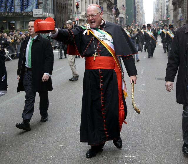 The Grand Marshall of the St. Patrick's Day Parade, ArchbishopTimothy Dolan, walks past protesters during the St. Patrick's Day Parade in New York, Tuesday, March 17, 2015. (Photo by Seth Wenig/AP Photo)