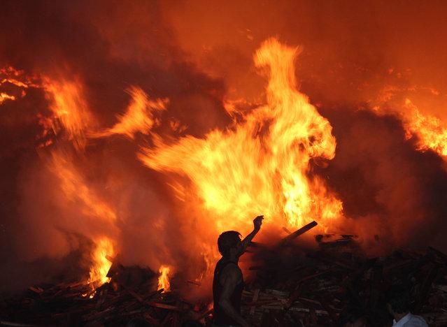 Firefighters battle a blaze in slums behind an industrial area at Bazar Khala in Uttar Pradesh, India on November 13, 2015. (Photo by Azam Husain/Barcroft India)