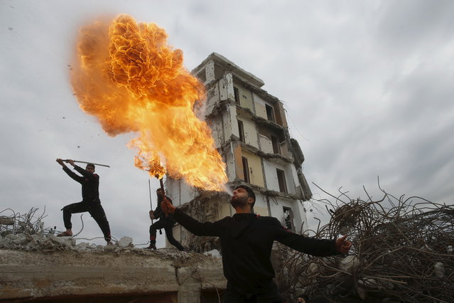 A Palestinian youth blows fire as he demonstrates his ninja-style skills for a photographer in front of the ruins of a building, that was destroyed in the 2014 war, in the northern Gaza Strip January 29, 2016. (Photo by Mohammed Salem/Reuters)