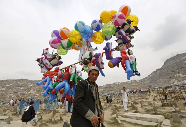 A man carries toys for sale during celebrations for Afghan New Year (Newroz) in Kabul March 21, 2015. (Photo by Mohammad Ismail/Reuters)