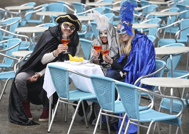 Masked revellers pose with their drinks in San Marco Piazza during the Venice Carnival, January 30, 2016. (Photo by Alessandro Bianchi/Reuters)