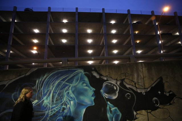 A woman walks by graffiti artwork in Des Moines, Iowa, January 23, 2015. (Photo by Jim Young/Reuters)