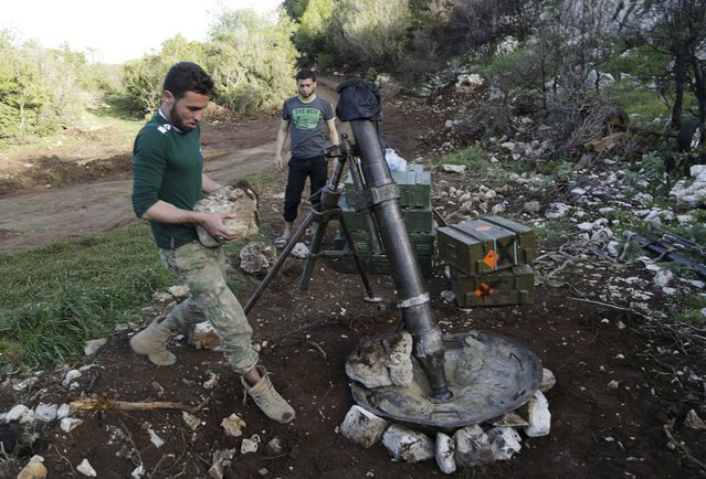 """Rebel fighters of """"Ahrar Jableh"""" brigade prepare to launch a mortar in the Jabal al-Akrad area in Syria's northwestern Latakia province April 28, 2015. (Photo by Khalil Ashawi/Reuters)"""