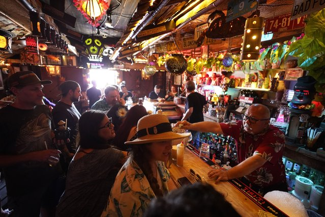 Patrons enjoy cold tropical cocktails in the tiny interior of the Tiki-Ti bar as it reopens on Sunset Boulevard in Los Angeles, Wednesday, July 7, 2021. Los Angeles County public health officials have urged people to resume wearing masks indoors regardless of their vaccination status. (Photo by Damian Dovarganes/AP Photo)