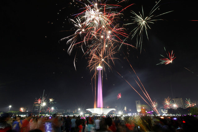 People watch fireworks explode around the National Monument during New Year's Eve celebrations in Jakarta, Indonesia January 1, 2017. (Photo by Fatima El-Kareem/Reuters)