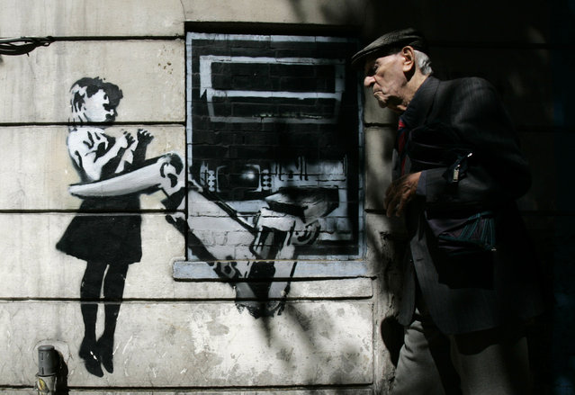 A man walks past a graffiti creation by Banksy at Exmouth Market in London in 2007. (Photo by Luke MacGregor/Reuters)