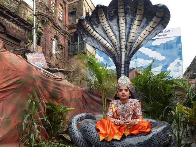 An young Indian Jain devotee dressed as Lord Krishna participates in a religious rally organised on the occasion of Mahavir Jayanti in Kolkata on April 2, 2015. The most important religious holiday in Jainism, Mahavir Jayanti celebrates the birth of Mahavira, the last Tirthankara, which is generally accepted as 599 BCE. (Photo by Dibyangshu Sarkar/AFP Photo)
