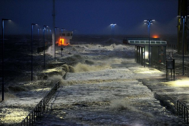 Waves lash the ferry pier on the North Sea coast in Dagebuell, Germany, on December 5, 2013 as storm front Xaver hits Germany. (Photo by Carsten Rehder/AFP Photo/DPA)