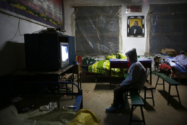 A student watches a film about Mao Zedong in a dormitory at the Democracy Elementary and Middle School in Sitong town, Henan province December 4, 2013. (Photo by Carlos Barria/Reuters)