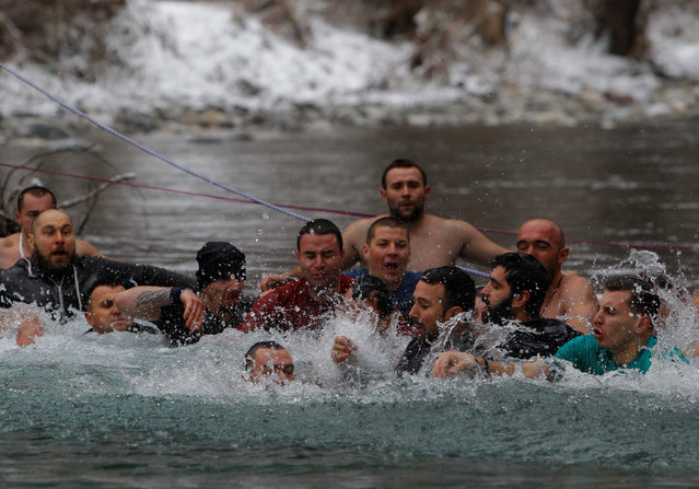 Men scramble in the water to find the cross during the Epiphany day celebration in Bitushe, Macedonia January 19, 2017. (Photo by Ognen Teofilovski/Reuters)