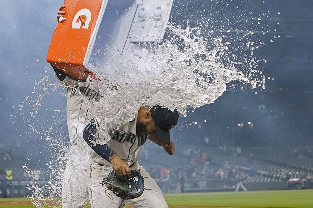 Seattle Mariners' Abraham Toro, right, has a cooler of water dumped on him by teammate Luis Torrens, left, as Toro takes part in an interview after a baseball game against the Houston Astros, Tuesday, August 31, 2021, in Seattle. Toro hit a grand slam in the eighth inning to give the Mariners a 4-0 win. (Photo by Ted S. Warren/AP Photo)