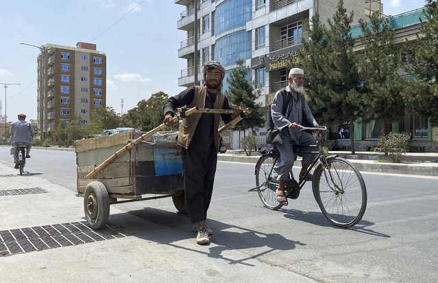 Sal Mohammad, 25, an Afghan man who gathers pieces of iron from the street to sell for scrap, pushes his handcart in Kabul, Afghanistan, Tuesday, August 31, 2021. (Photo by Sayed Ziarmal Hashemi/AP Photo)