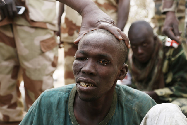 "A man, whom the Chadian military say they have taken prisoner for belonging to insurgent group Boko Haram, is seen in Gambaru, February 26, 2015. Accused of killing five people the way Boko Haram does, cutting their throat with a knife, the soldiers gave him a nickname: ""The Butcher"". (Photo by Emmanuel Braun/Reuters)"