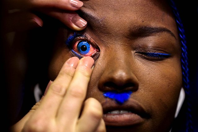 A model gets prepared with a blue contact lens to present a creation of Patrick Mohr's Autumn Winter 2014 collection during Mercedes Benz Fashion Week in Berlin, on January 14, 2014. (Photo by Markus Schreiber/Associated Press)