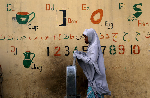 A girl draws water from a fountain a day after the postponement of the presidential election in Kano, Nigeria on February 17, 2019. (Photo by Luc Gnago/Reuters)