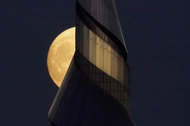 The waxing moon rises beyond the 300-foot-tall stainless steel spire at the Community of Christ temple Sunday, September 19, 2021, in Independence, Mo. (Photo by Charlie Riedel/AP Photo)