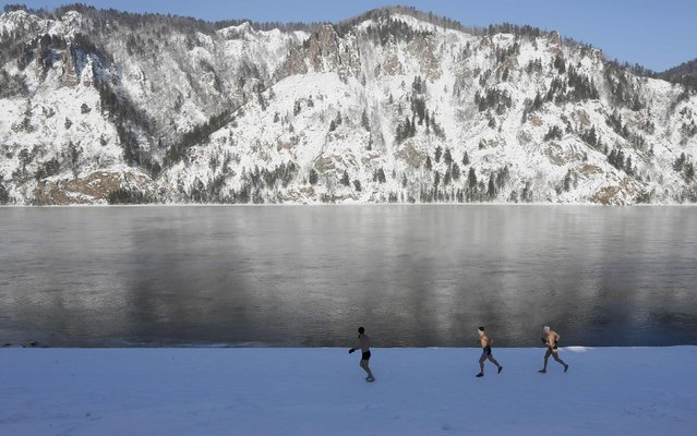 Enthusiasts of winter swimming warm up on the bank of the Yenisei River ahead of their weekly bathing session, with the air temperature at about minus 26 degrees Celsius (minus 14.8 degrees Fahrenheit), in the Siberian town of Divnogorsk, Russia January 27, 2017. (Photo by Ilya Naymushin/Reuters)