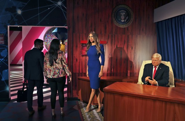 People visit the wax versions of former U.S. President Donald Trump and his wife Melania at the opening of the Madame Tussauds museum, in Dubai, United Arab Emirates, Wednesday, October 13, 2021. The lavish waxworks temple located on a small artificial island off Dubai unveiled 60 celebrities and leaders, from a sultry Kylie Jenner to a beaming Chinese President Xi Jinping, along with a handful of Bollywood dance stars striking poses. (Photo by Kamran Jebreili/AP Photo)