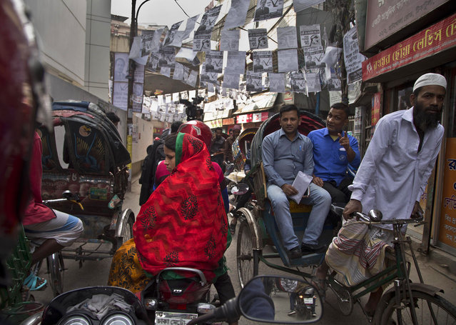 Election posters are seen hanging as Bangladeshi rickshaw pullers transport passengers in Dhaka, Bangladesh, Thursday, December 27, 2018. Bangladesh heads for the 11th National Parliamentary Election on Dec. 30, amid opposition allegations that thousands of its leaders and activists have been arrested to weaken them. But authorities say the arrests are not politically motivated and the opposition is trying to create chaos ahead of elections. (Photo by Anupam Nath/AP Photo)