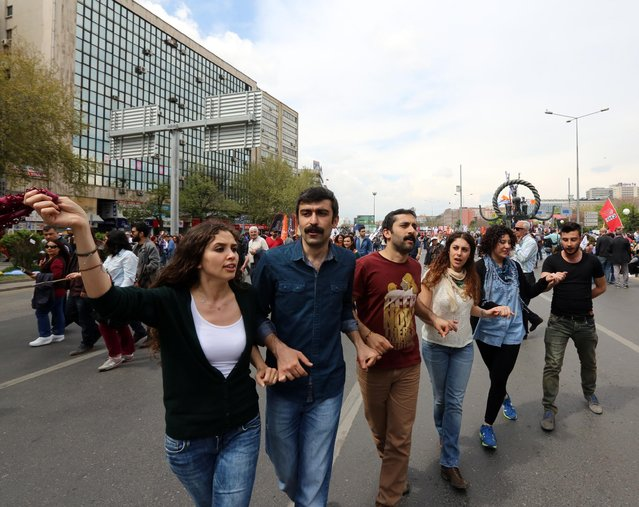 Turkish students dance during May Day celebrations in Ankara, Turkey, Friday, May 1, 2015. Riot police and May Day demonstrators clashed in Istanbul as crowds determined to defy a government ban tried to march to the city's iconic Taksim Square. Security forces pushed back demonstrators using water cannons and tear gas. (Photo by Burhan Ozbilici/AP Photo)