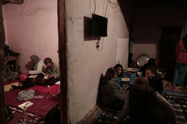 In this March 30, 2019 photo, women eat in Umm Yasser's home in Wadi Sahw, Abu Zenima, in South Sinai, Egypt. (Photo by Nariman El-Mofty/AP Photo)
