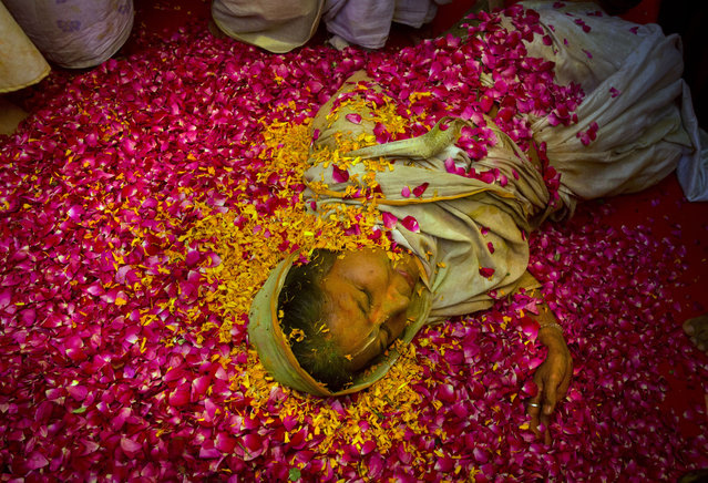 An Indian Hindu widow lies on a bed of   flower petals during Holi celebrations at the Gopinath temple, 180 kilometres (112 miles) south-east of New Delhi, India Monday, March 21, 2016. (Photo by Manish Swarup/AP Photo)