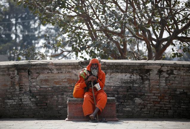 A Hindu holy man, or sadhu, sits at the premises of Pashupatinath Temple, ahead of the Shivaratri festival in Kathmandu, Nepal February 15, 2017. (Photo by Navesh Chitrakar/Reuters)