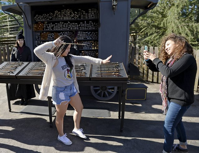 "A guest poses with a magic wand during a soft opening and media tour of ""The Wizarding World of Harry Potter"" theme park at the Universal Studios Hollywood in Los Angeles, California in this picture taken March 22, 2016. (Photo by Kevork Djansezian/Reuters)"