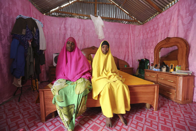 Saciido Sheik Yacquub, 34, poses for a picture with her daughter Faadumo Subeer Mohamed, 13, at their home in Hodan district IDP camp in Mogadishu February 11, 2014. Saciido, who runs a small business, wanted to be a business woman when she was a child. She studied until she was 20. She hopes that Faadumo will become a doctor. Faadumo will finish school in 2017 and hopes to be a doctor when she grows up. (Photo by Feisal Omar/Reuters)