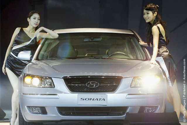 Models pose next to the new mid-sized sedan 'NF Sonata' unveiled by Hyundai Motor