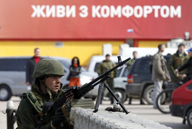 """An armed man, believed to be a Russian serviceman, guards near the naval headquarters in Sevastopol, March 19, 2014. Around a dozen Ukrainian servicemen, unarmed and in civilian clothes, walked out of the Ukrainian naval headquarters in the Crimean port of Sevastopol on Wednesday after it was taken over by pro-Russian forces, a Reuters witness said. The words in the background read, """"Live with comfort"""". (Photo by Vasily Fedosenko/Reuters)"""