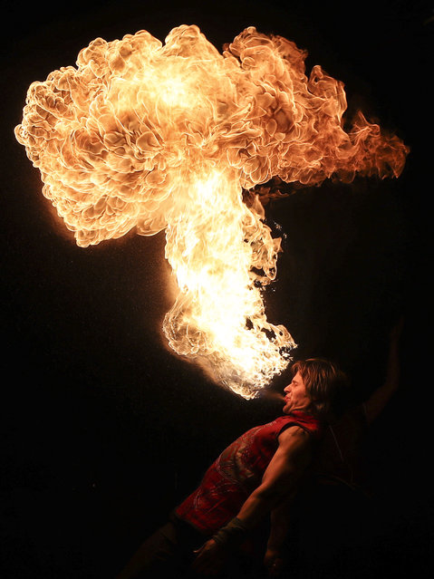 A man breathes out fire during the Phoenix Fire Festival at Lida Castle in Lida, Hrodna Region, Belarus on May 19, 2019. (Photo by Natalia Fedosenko/TASS)