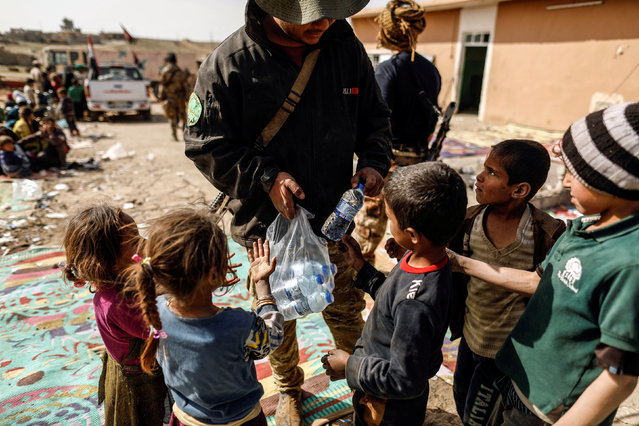 A special forces member gives bottles of water to displaced children, who just fled their homes, at their base as Iraqi forces battle with Islamic State militants, in western Mosul, Iraq February 28, 2017. (Photo by Zohra Bensemra/Reuters)