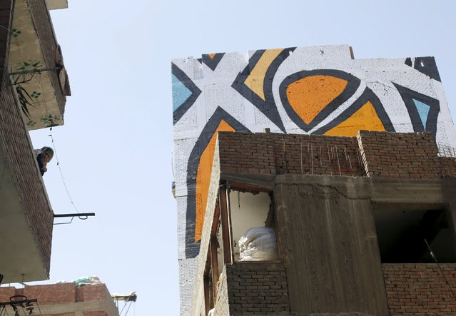 """A woman looks on from her balcony, near parts of a mural painted on the walls of houses in Zaraeeb, created by French-Tunisian artist El Seed, in the shanty area known as Zabaleen or """"Garbage City"""" on the Mokattam Hills in eastern Cairo, Egypt, April 4, 2016. (Photo by Amr Abdallah Dalsh/Reuters)"""