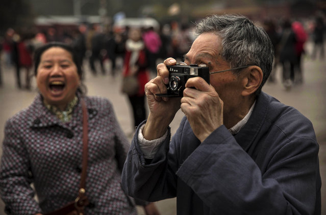 A Chinese man uses an old film camera to take a picture of relatives near the Forbidden City on March 27, 2014 in Beijing, China. (Photo by Kevin Frayer/Getty Images)