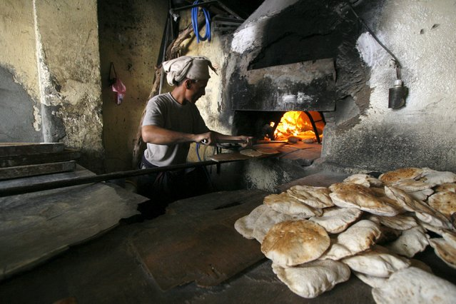 A baker uses firewood amid an acute fuel shortage in Yemen's southwestern city of Taiz May 19, 2015. (Photo by Reuters/Stringer)