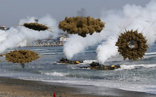 Amphibious assault vehicles of the South Korean Marine Corps throw smoke bombs as they move to land on shore during a U.S.-South Korea joint landing operation drill in Pohang March 31, 2014. The drill is part of the two countries' annual military training called Foal Eagle, which began on February 24 and runs until April 18. (Photo by Kim Hong-Ji/Reuters)