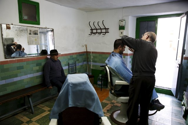 "Manolo Carrasco, 75, cuts Juan Francisco Ortega's hair in his family barbershop in the hometown of Don Quixote's ladyship Dulcinea, in El Toboso, Spain, April 6, 2016. ""My father had a basin like the one Don Quixote used as a helmet hanging outside the barbershop, but children used to throw rocks at it and he ended up taking it down"", Carrasco says. Now that his father is gone (he worked at the barbershop until 84 and passed away at the age of 95) he keeps it at home. (Photo by Susana Vera/Reuters)"